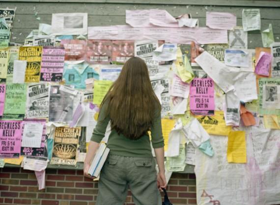 девушка стоит перед доской с объявлениями