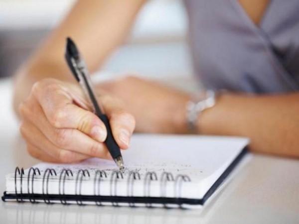 Девушка пишет в тетрадке